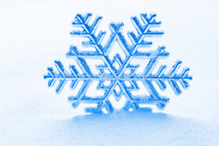 Snowflake against a background of snow. Snowflake ornament against a background of snow Royalty Free Stock Images