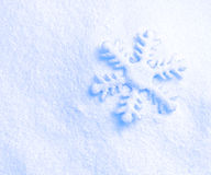 Snowflake against a background of snow Stock Image