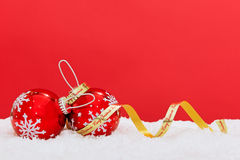 Snowflake baubles and ribbon on red background. Royalty Free Stock Photo