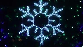 Snowflake bokeh. Flashing snowflake Rasfokus on the background of the Christmas tree stock footage
