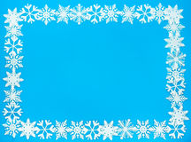 Snowflake Border and Background Frame. Snowflake Frame out of artificial white snowflakes on solid blue background stock photography