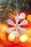 Snowflake on branch of Christmas tree Stock Photo