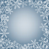 Snowflake card. Winter background. Frame made of fluffy snowflakes on soft blue background with space for text Royalty Free Stock Images