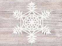 Snowflake carved from paper on light brown board Stock Images