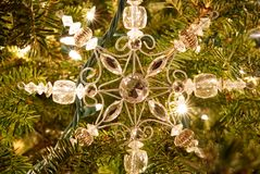 A snowflake Christmas ornament on a fur tree. A closeup of a snowflake Christmas ornament hanging on a fur tree with lights in the background royalty free stock photo