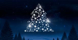 Snowflake Christmas tree pattern shape glowing in Winter night sky. Digital composite of Snowflake Christmas tree pattern shape glowing in Winter night sky Stock Photography