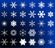 Snowflake Collection. A collection of traditional snowflake shapes in white on a blue background Royalty Free Stock Photos