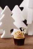 Snowflake cupcake on Christmas background. Snowflake cupcake on white Christmas trees background Royalty Free Stock Image