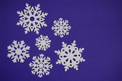 Snowflake cut outs on blue purple background Royalty Free Stock Image