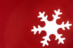 Snowflake cutout. Paper punched snowflake closeup; red coated cardstock Royalty Free Stock Photo
