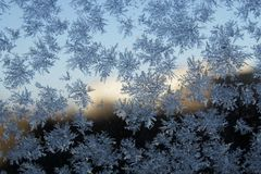 Snowflake on the glass. A snowflake is a single ice crystal that has achieved a sufficient size, and may have amalgamated with others, then falls through the royalty free stock photo