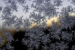 Snowflake on the glass. A snowflake is a single ice crystal that has achieved a sufficient size, and may have amalgamated with others, then falls through the stock photo