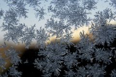 Snowflake on the glass. A snowflake is a single ice crystal that has achieved a sufficient size, and may have amalgamated with others, then falls through the royalty free stock photos