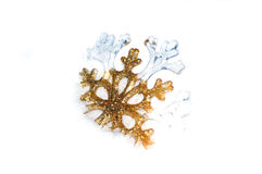 Snowflake golden in snow on white background Stock Photography