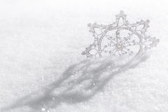 Snowflake. A hand-crafted fabric snowflake on a fresh snow Royalty Free Stock Photography