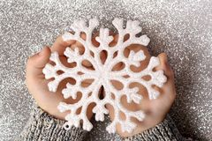 Snowflake in hands. On glitter background Stock Photo