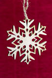 Snowflake hanging on a rope on a red background, new year, Chris Stock Photos