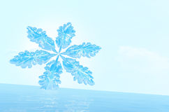 Snowflake on ice against a background of the bright blue sky. Stock Images