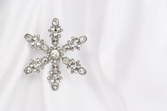 Snowflake - Jeweled on Satin. Ornamental jeweled snowflake on white satin background Royalty Free Stock Photos
