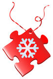 Snowflake puzzle gift. Red puzzle piece amulet christmas present with snowflake and string Stock Photography