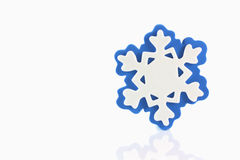Snowflake with reflection. Blue snowflake with reflection on white background royalty free stock photography