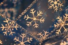 Snowflake Ribbon Closeup. Macro of blue sheer holiday ribbon with white snowflake design and silver highlights royalty free stock photos