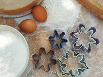 Snowflake shape cookies cutters, eggs, flour in a bowl, linen napkin on vintage wooden board for Christmas cookies. Royalty Free Stock Photography