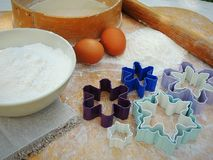 Snowflake shape cookies cutters, eggs, flour in a bowl, linen napkin on vintage wooden board for Christmas cookies. Stock Photography