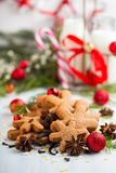 Snowflake shaped Cookies and spices. Some homemade gingerbread cookies with spices and Christmas decorations on background Royalty Free Stock Images