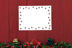 Snowflake sign with Christmas garland border and presents hanging on antique red wooden background Stock Images