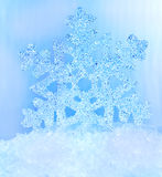 Snowflake in snow on blue. Stock Image