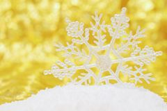 Snowflake in snow with gold background Royalty Free Stock Image