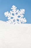 Snowflake in snow on sky background Stock Photos