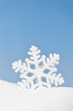 Snowflake in snow on sky background Royalty Free Stock Photo