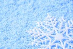 Snowflake in snow. White snowflake in blue snow Royalty Free Stock Photo