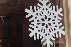 Snowflake. Sparkly bright white felt snowflake in window Stock Image