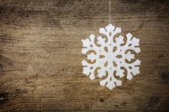 Snowflake star hanging over a rustic wooden background as a chri Royalty Free Stock Photo
