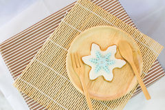 Snowflake sugar cookie on dish Royalty Free Stock Image