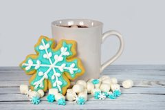 Snowflake sugar cookie with hot cocoa drink. Hot chocolate drink with snowflake sugar cookie and marshmallows on rustic whitewashed wood Royalty Free Stock Images