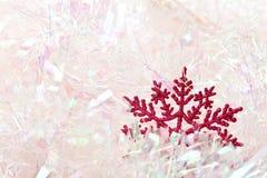 Snowflake in tinsel. Reg glitter snowflake sitting in pink tinsel Stock Images