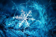 Snowflake on wool. Macro background snowflake on wool royalty free stock image