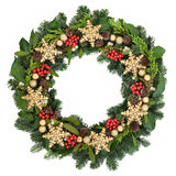 Snowflake Wreath. Christmas wreath with gold snowflake and bauble decorations, holly, ivy, mistletoe and winter greenery over white  background Royalty Free Stock Photo