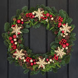 Snowflake Wreath. Christmas wreath with gold snowflake bauble decorations, holly, mistletoe and winter greenery over dark oak front door background stock photography
