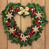 Snowflake Wreath. Christmas heart shaped wreath with gold snowflake bauble decorations, bow, holly, mistletoe and winter greenery over oak front door background royalty free stock photos