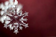 Snowflakeprydnad på röd bakgrund Arkivfoto