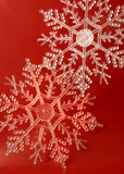 Snowflakes. Glittery snowflake ornaments on a red background Royalty Free Stock Photo