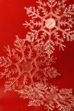 Snowflakes. 3 Glittery snowflake ornaments on a red background Royalty Free Stock Photography