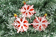 Snowflakes on the background of green tinsel Stock Photos