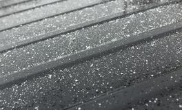 Snowflakes on a black car as a background.  Royalty Free Stock Photography