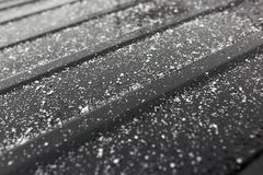 Snowflakes on a black car as a background.  Stock Images